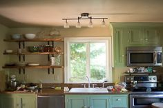 what real farmhouse kitchens look like - beautiful | open shelving, track lighting, green painted cabinets