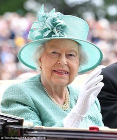 The Queen waves to the crowds as she makes her entrance at Royal Ascot
