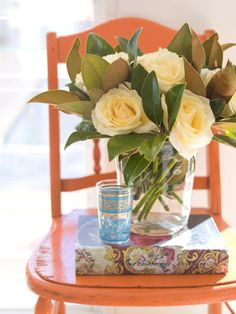 Vignette:  Orange chair, book, juice glass and jar of roses.  So beautiful.