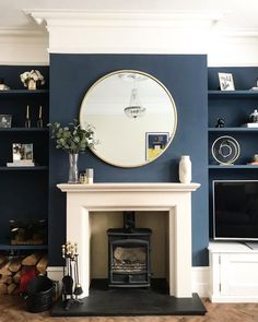 Beautiful dark blue wall in the living room with cream mantelpiece, wood burner . : Beautiful dark blue wall in the living room with cream mantelpiece, wood burner and oversized round mirror. Cream Living Rooms, Dark Blue Living Room, Dark Blue Walls, Living Room Grey, Home Living Room, Navy Walls, Mirrors In Living Room, Dark Blue Lounge, Apartment Living