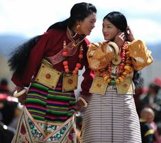 Beautiful Tibetan women from near Dabpa, Kham (or Daocheng, Yunnan for the Chinese) dressed in her finest brocade and traditional accessories at a summer horse race festival. I'm curious about the girl on the right wearing a bindi: