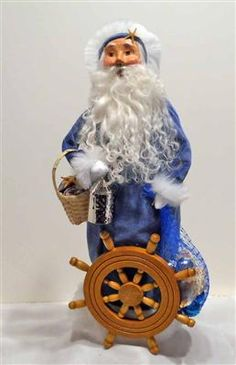 """This Santa can extend your Byers Choice Caroler display season clear into summer.  He carries a ships wheel, a basket  of sea shells & a star fish.  His robe is a cool blue  with white trim. 13"""" tall. Cute to display with your collection of sea shells or sea glass."""