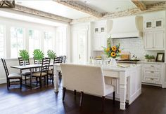 Creamy white kitchen, painted in Benjamin Moore OC-37 Glacier White, distressed whitewashed ceiling beams and dark stained hardwood floors.