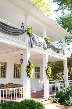 Old Southern charm shows through the decor on the front of the house at Cedarwood. The combination of linens and flowers here brings an elegant touch to the front of the property where the guests will be welcomed.    www.cedarwoodweddings.com