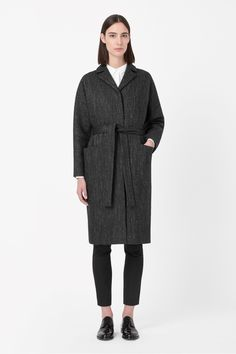 A long style, this oversized wool coat has a modern herringbone design  and matching tie-fastening belt. With curved shoulder seams and kimono sleeves, it has notched lapels, deep front pockets and a comfortable cotton lining. It is secured with hidden buttons along the front.