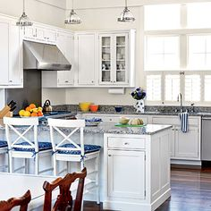 Granite countertops and Shaker-style painted cabinets in the kitchen give the space a warm, transitional aesthetic. | Coastalliving.com