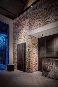 Idee hal. Hoge muur met steenstrips. Deur bv meeterkast in zelfde hout als trap, keuken etc.. Breekt het steriele strakje van de witte stuk wanden verder in huis.