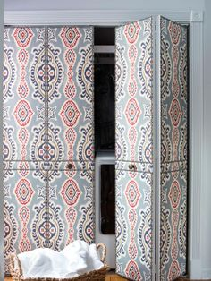 To add charm to basic bifold doors, cover them in batting then upholster with a colorful yet traditional fabric, like these laundry room doors. Finish with a classic bronze nail-head trim.
