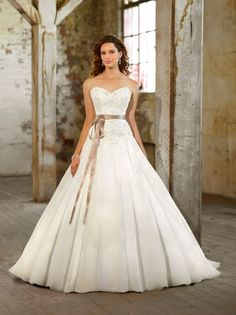 STYLE D1355 - This strapless designer ball gown is made of Royal Organza and features a beautiful bodice of jewel beading and lace. The gently pleated skirt adorned with secret sparkle floats light as air, while a French ribbon at the waist adds balance. Choose from lace up or zip up back closure.
