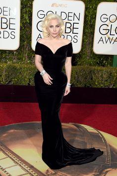 """Não há nada Gaga sobre esse look!  Lady Gaga escorria velho glamour de Hollywood em um veludo Atelier Versace vestido deslumbrante nas 73rd Annual Golden Globe Awards em 10 de janeiro de 2016. A 29-year-old entertainer ganhou o prêmio de Melhor Performance de uma Atriz em Minissérie ou um Motion Picture feito para a televisão por seu trabalho na série """"American Horror Story: Hotel"""", sua primeira indicação e ganhar como atriz."""