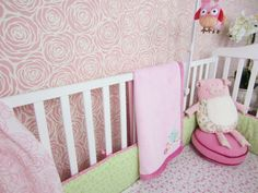 A pink and white DIY stenciled accent wall in a nursery using the Roses Allover Stencil from Cutting Edge Stencils. http://www.cuttingedgestencils.com/roses-stencil-pattern-rose-design.html