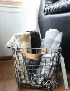 cozy scandinavian spring hygge style | blankets in a wire industrial basket with leather handles La Petite Farmhouse