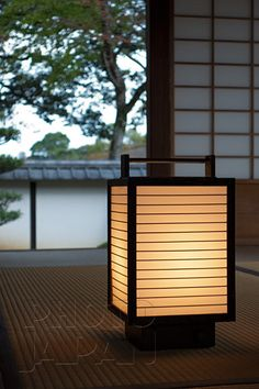 Japan - Glowing washi lantern on tatami mat floor with garden view through open shoji - Photo by Photo Japan