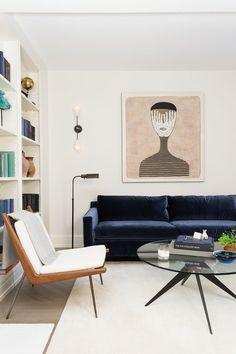 Blue Velvet Sofa with cream rug and white chair