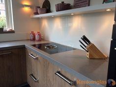Houten keuken met een grijze beton-look blad, afgewerkt met een witte #Keukenglas #achterwand. #keukeninspiratie #backsplash #splashback #kitcheinspiration #spatwand #glaswand www.keukenglas.nl