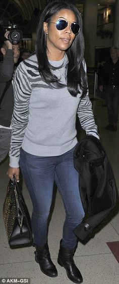These boots are made for walking: Gabrielle sported jeans, a grey sweater and aviator sunglasses after her flight
