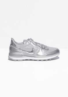 NIKE These sneakers have a retro running shoe style, combining patent details and nylon upper.
