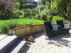 Deze tuinfoto's zijn ca. 6 weken na de tuinaanleg gemaakt. Zo snel kun je al resultaat hebben als je op tijd tuinplannen maakt. Mooie vrolijke verharding van gebakken tegels 20x20, gecombineerdmet tegels van 30x60. De gebogen keerwand aan het water is een opsluiting of grondkering gemaakt van…