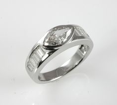 14k white gold engagement ring with bezel set marquise diamond and baguettes.