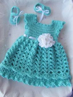 This listing is for baby girl 3-piece outfit. The dress is made out of a soft robins egg blue yarn with a white ribbon that ties in back of the dress. There is a white sparkly flower attached to the front. The shoes and the headband are made from the same blue and white yarn to match.