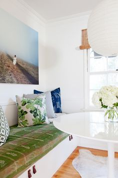 Breakfast nook with patterned pillows, a beachy photograph, and a big white pendant light