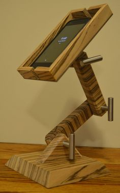 Made of walnut, this will work and look stylish in any place you need to set and see your phone. With slots on either side for charging cords, it can be out of the way or the centerpiece of your desk. Wood Shop Projects, Small Wood Projects, Cool Woodworking Projects, Woodworking Furniture, Wooden Phone Holder, Cell Phone Holder, Diy Phone Stand, Wood Cutter, Support Telephone