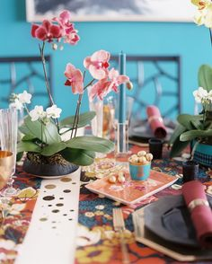 A festive table set with colorful runners and potted orchids.