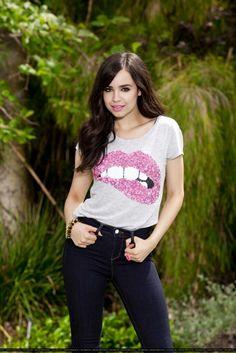 sofia carson posing in a lip shirt .