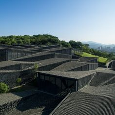 Curved tiles cover the individual pitched roofs of the folk-art galleries Kengo Kuma & Associates designed for the China Academy of Arts