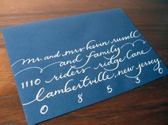 This is almost what ours will look like!  Well, the white on blue at least. No guarantees on my calligraphy skills (or lack thereof)    white calligraphy address on navy envelope from Trail by Cupcakes