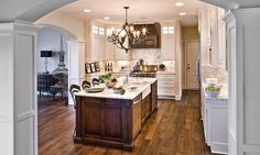 In love with the antique white cabinetry  with creamy granite, accented by the dark hardwood floor and brown island.  LOVE IT!