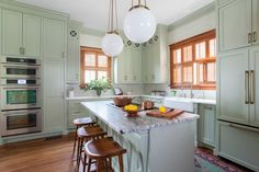 HGTV presents a light green cottage-style kitchen that ties in with the overall home's Victorian style through the use of detailed wallpaper and other elements. The room also features modern appliances and a spacious eat-in island for added convenience.