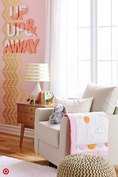 Bring your baby's nursery to life with a few easy touches. Start by adding an accent wall for a focal point. Sprinkle in warm, gold hues, such as chevron wall decals, and add colorful letters that spell a favorite saying. A coordinating crib bedding set helps pull together your color scheme. Furnishings in soft neutrals, including a gray upholstered armchair and cozy rug, plus a textured pouf, ground the room. You'll have a soothing spot for rocking your baby—up, up & away to dreamland.