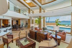Floor-to-ceiling windows offer incredible views of the Pacific Ocean from the living room and kitchen. Brown leather and wood furniture grounds the lofty space.