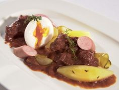 Fiakergulasch is a Viennese version of the spicy Puszta dish. A ragout made with beef which is topped with sausage, fried egg and gherkins with a warming sauce. Austrian Cuisine, Austrian Food, Slow Carb Recipes, Austrian Recipes, Goulash, Spicy, Sausages, Treats, Dishes