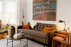 Orange throw pillows are just what this setting needs to break up the brown. Paired with the white throw, the two help the couch stand out in a room full of neutrals.