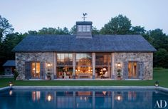 G. P. Schafer Architect, this Connecticut poolhouse takes the shape of a sophisticated barn with stone walls and weathered plank shutters.