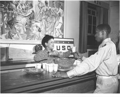 A Black American serviceman, being greeted at the front desk of a USO Center, 1943.