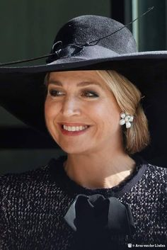 For this event, she repeated her large black velvet felt Garbo hat with curved brim. For a dramatic hat, the embellishment on this design is surprisingly subdued- just a curved quill and knotted grosgrain ribbon hat band. While the trim is low key, the scale and presence of this hat is most grand and on Máxima, it makes a dramatic and fantastic millinery statement.