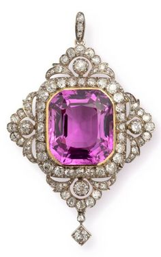 An antique topaz and diamond pendant, Imperial Presentation, circa 1900. Centred by an extraordinary pink topaz of unusually intense colour, surrounded by a border of old European cut diamonds, each side embellished with diamond set opposing foliate curves beneath arches with diamond centres, a square mounted diamond suspended beneath. #antique #pendant