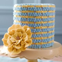 Shell Weave & Fantasy Flower Cake - Icy blue shells thread their way through bands of yellow and gray on a cake that adds a touch of springtime to any time of year. A lush fantasy flower, with petals cut using the Hearts Double Cut-Outs Set, provides a beautiful finishing touch.