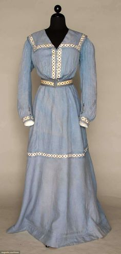 Summer seaside dress, circa 1890-1902. Two-piece light blue chambray with self-fabric belt, tiny mother of pearl buttons on front. Cord closures, sailor collar, pintucks. All pieces are inset with navy blue embroidered white cotton bands. Via Augusta Auctions.