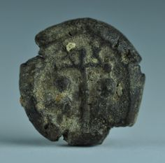 True cross clay token with the emblem of the cross and X on horizontal side bars and two figures that could be Apostle Peter and St. Paul, 1.6 cm diameter. Private collection
