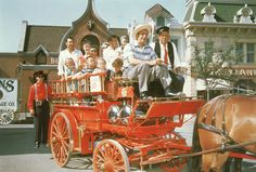 Walt takes the reigns of a red, horse-drawn fire wagon for a ride around Main Street. | 18 Wonderful And Rare Color Photos Of Disneyland In 1955