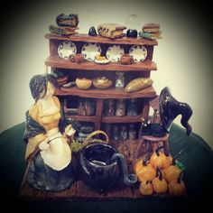 A Witches work is never done....Handcrafted ceramic sculpture of a witch in her kitchen holding a willow wand and her pet crow, her black cat sits on a chair by the dresser. The cauldron can be used to burn incense cones. these witches kitchens are on of a kind and made to order to customers  specifications.