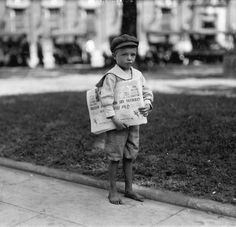 A 7 year old named Ferris selling newspapers on a street corner. He is likely a homeless orphan, as thousands of other 'newsies' were at the turn of the 20th century. Mobile, Alabama, 1914.