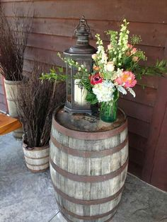 Entrance centerpiece atop a whiskey barrel with a lantern. Our in-house floral designer has a great talent for using beautiful arrangements with other decor to create any Style or look the Client wishes.