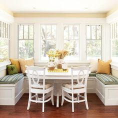 I love how this cozy nook was created by partnering a worn farm table, chairs and a padded banquette.