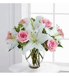 PINK ROSE AND WHITE LILY BOUQUET Floral bouquet/arrangement with gorgeous fresh pink roses with showy white lilies in a glass vase.