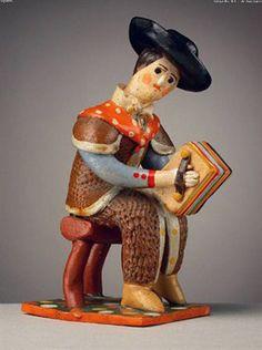 Pastor de lenço ao pescoço, a tocar harmónio sentado (13,9 x 5,5 cm). Autor desconhecido (séc. XX). Museu Nacional de Etnologia, Lisboa.